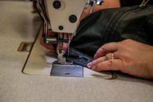 dipendente movimoda esegue cuciture su capo di abbigliamento maschile
