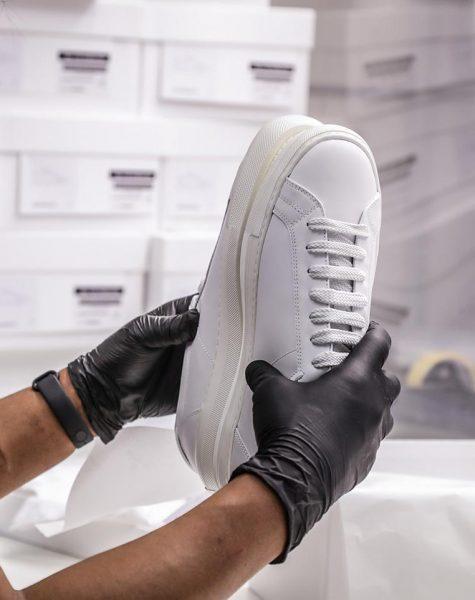 controllo qualità su scarpe bianche