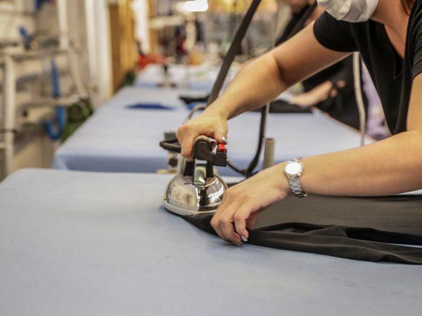 operaia stira capo di abbigliamento al termine della filiera di produzione